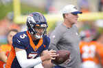 Denver Broncos quarterback Drew Lock, front, takes part in drills as offensive coordinator Pat Shurmur follows the play at an NFL football training camp Tuesday, Aug. 3, 2021, at team headquarters in Englewood, Colo. (AP Photo/David Zalubowski)