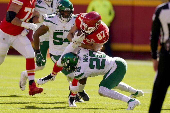 Kansas City Chiefs tight end Travis Kelce (87) breaks through tackle attempts by New York Jets' Avery Williamson (54) and Marcus Maye (20) as Kelce catches a pass for a first down in the first half of an NFL football game on Sunday, Nov. 1, 2020, in Kansas City, Mo. (AP Photo/Charlie Riedel)