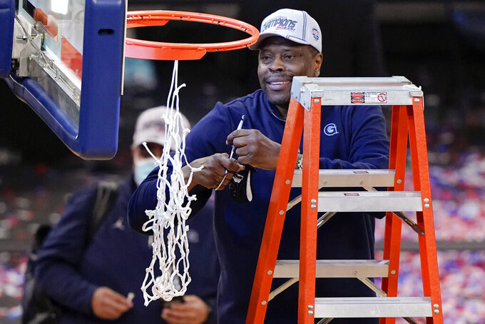 Georgetown head coach Patrick Ewing cuts down the net after an NCAA college basketball game against Creighton in the championship of the Big East Conference tournament Saturday, March 13, 2021, in New York.  (AP Photo/Frank Franklin II)