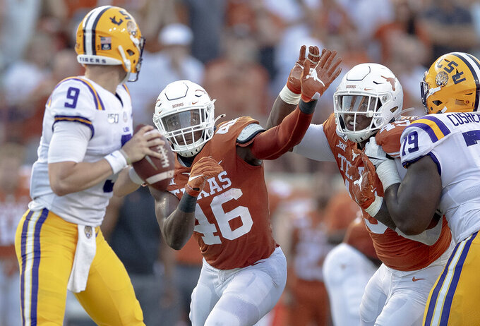 FILE - In this Saturday, Sept. 7, 2019 file photo, Texas linebacker Joseph Ossai (46) and defensive lineman Peter Mpagi (45) rush LSU quarterback Joe Burrow (9) during an NCAA football game in Austin, Texas. (Nick Wagner/Austin American-Statesman via AP, File)