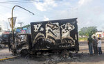 A burnt out truck used by gunmen smolders on an intersection, a day after street battles between gunmen and security forces in Culiacan, Mexico, Friday Oct. 18, 2019. Mexican security forces backed off an attempt to capture a son of imprisoned drug lord Joaquin