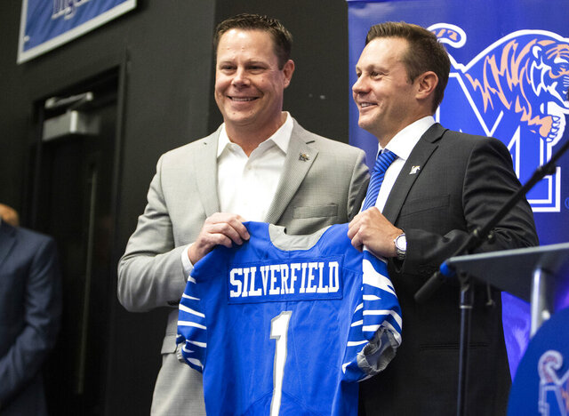 FILE - In this Dec. 13, 2019, file photo, Memphis director of athletics Laird Veatch, left, presents Memphis head football coach Ryan Silverfield, right, with a team jersey in Memphis, Tenn. As football players start returning to campus, college officials have a wide range of opinions on whether to let the public know how many of their athletes test positive for coronavirus.  Just over half of the 64 Football Bowl Subdivision members that responded to an Associated Press survey said they were still deciding whether to announce the number of student-athletes with positive tests.(Ariel Cobbert/The Commercial Appeal via AP, File)