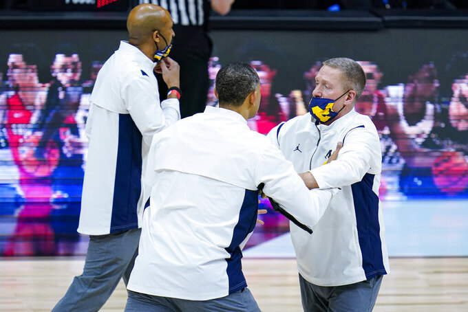 Michigan head coach Juwan Howard, center, is restrained after being ejected from the game in the second half of an NCAA college basketball game against Maryland at the Big Ten Conference tournament in Indianapolis, Friday, March 12, 2021. (AP Photo/Michael Conroy)