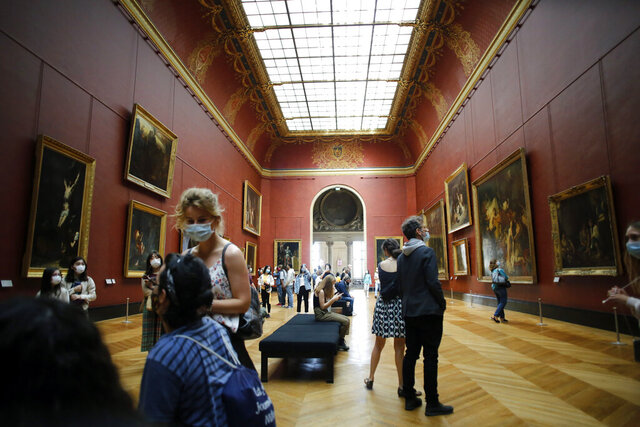 Visitors watch pantings at the Louvre Museum, in Paris, Monday, July 6, 2020. The home of the world's most famous portrait, the Louvre Museum in Paris, reopened Monday after a four-month coronavirus lockdown. (AP Photo/ Thibault Camus)