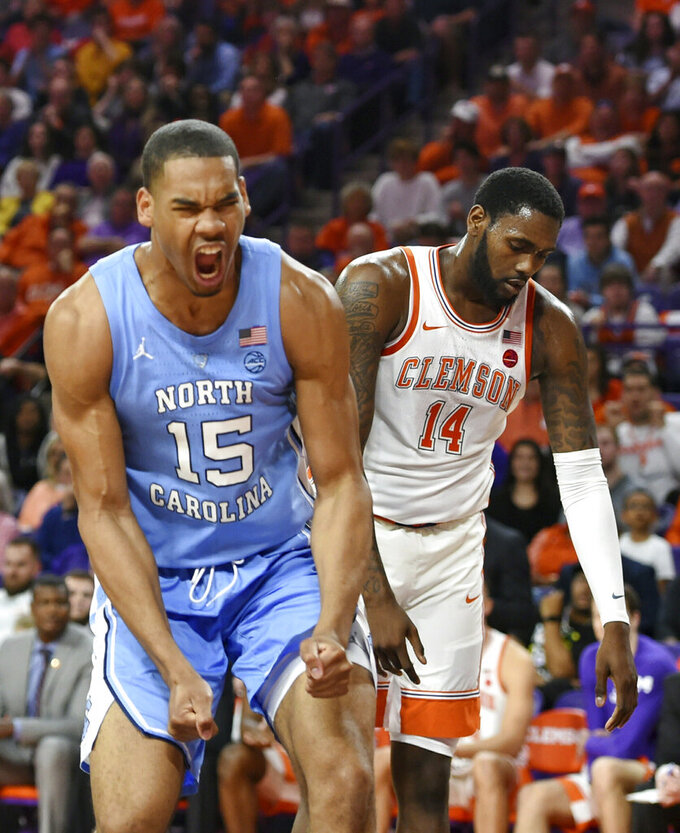 North Carolina's Garrison Brooks reacts after scoring while defended by Clemson's Elijah Thomas (14) during the first half of an NCAA college basketball game Saturday, March 2, 2019, in Clemson, S.C. (AP Photo/Richard Shiro)