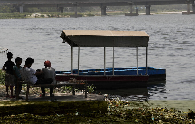 People sit in the shade on the banks of the river Yamuna in New Delhi, India, Thursday, May 28, 2020. India grappled with scorching temperatures and the worst locust invasion in decades as authorities prepared for the end of a months long lockdown despite recording thousands of new infections every day. (AP Photo/Manish Swarup)