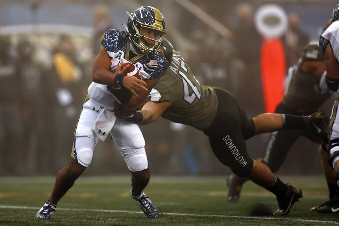 Navy quarterback Xavier Arline (7) is tackled by Army linebacker Jon Rhattigan (47) during the first half of an NCAA college football game Saturday, Dec. 12, 2020, in West Point, N.Y. (AP Photo/Adam Hunger)