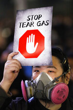 A protester wearing a gas mask holds a sign reading