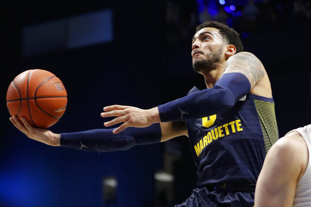 FILE - In this Jan. 29, 2020, file photo, Marquette's Markus Howard (0) shoots against Xavier's Jason Carter, obscured at right, during the first half of an NCAA college basketball game in Cincinnati. Howard will leave Marquette as one of the most dynamic scorers in Big East history. He has the most career points of any active Division I player and leads the nation in points per game this season. The one achievement that has eluded the 5-foot-11 senior guard is an NCAA Tournament victory. Howard is seeking one last chance to rectify that as he caps an otherwise illustrious college career. (AP Photo/John Minchillo, File)