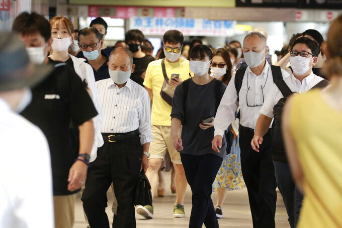 People wearing face masks to protect against the spread of the coronavirus walk at a train station in Tokyo Wednesday, July 28, 2021. Tokyo Gov. Yuriko Koike on Wednesday urged younger people to cooperate with measures to bring down the high number of infections and get vaccinated, saying their activities are key to slowing the surge during the Olympics. On Tuesday, the Japanese capital reported 2,848 new cases, exceeding its previous record in January. (AP Photo/Koji Sasahara)
