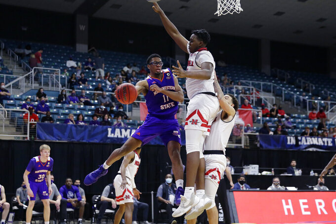 Northwestern State forward Jamaure Gregg (11) passes the ball around Nicholls State center Ryghe Lyons, right, during the second half of an NCAA college basketball game in the Southland Conference semifinals Friday, March 12, 2021, in Katy, Texas. (AP Photo/Michael Wyke)