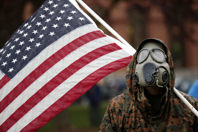 A protester wears a gas mask and carries an American flag during a rally in response to Michigan's coronavirus stay-at-home order at the State Capitol in Lansing, Mich., Thursday, May 14, 2020. (AP Photo/Paul Sancya)