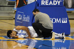 UCLA guard Jules Bernard, left, is aided by a trainer after going down with an injury during the first half of the team's NCAA college basketball game against Oregon State on Saturday, Jan. 30, 2021, in Los Angeles. (AP Photo/Marcio Jose Sanchez)