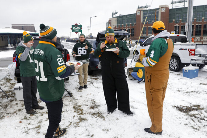 Fans tailgate outside of Lambeau Field before the NFC championship NFL football game between the Tampa Bay Buccaneers and Green Bay Packers in Green Bay, Wis., Sunday, Jan. 24, 2021. (AP Photo/Mike Roemer)