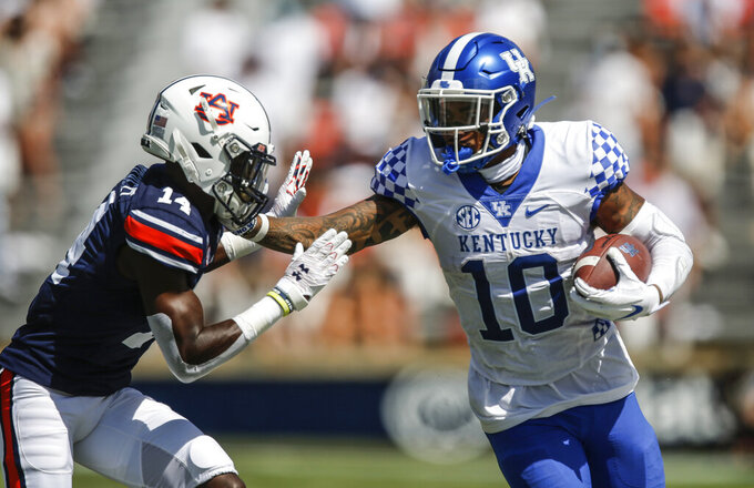Kentucky running back Asim Rose (10) stiff arms Auburn defensive back Traivon Leonard (14) as he carries the ball during the second quarter of an NCAA college football game on Saturday, Sept. 26, 2020 in Auburn, Ala. (AP Photo/Butch Dill)