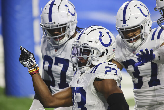 Indianapolis Colts cornerback Kenny Moore II (23) celebrates his 29-yard interception return for a touchdown with his teammates during the second half of an NFL football game, Sunday, Nov. 1, 2020, in Detroit. (AP Photo/Tony Ding)