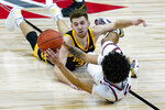 Illinois guard Andre Curbelo (5) makes a pass under Iowa guard Jordan Bohannon (3) in the second half of an NCAA college basketball game at the Big Ten Conference tournament in Indianapolis, Saturday, March 13, 2021. (AP Photo/Michael Conroy)