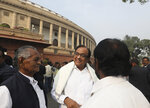 Indian lawmaker and former Finance Minister Palaniappan Chidambaram, center, talks to fellow lawmakers as he arrives at the Parliament House for a protest against the rise in onion prices, in New Delhi, India, Thursday, Dec. 5, 2019. Chidambaram, just released on bail in a bribery case, has joined a protest of the government's economic policies, which are being blamed for India's slowest economic growth in six years. (AP Photo/Manish Swarup)