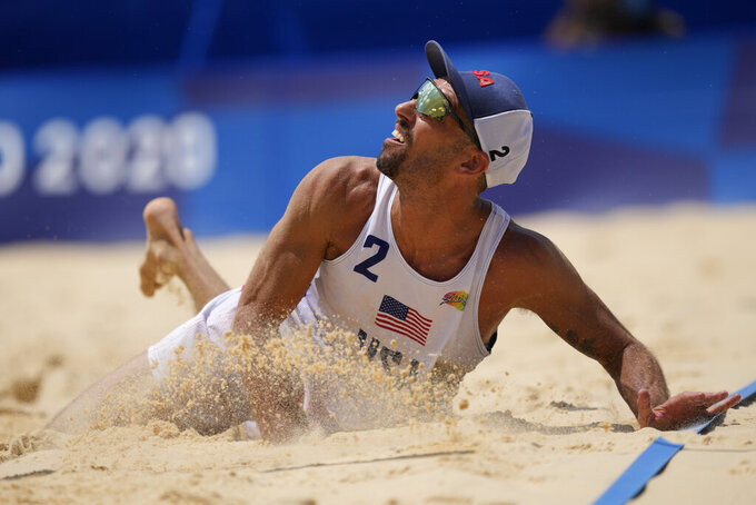 Nicholas Lucena, of the United States, hits the sand ad he competes during a men's beach volleyball match against Argentina at the 2020 Summer Olympics, Thursday, July 29, 2021, in Tokyo, Japan. (AP Photo/Petros Giannakouris)