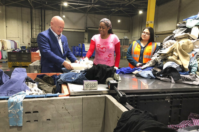 Democratic U.S. Senate candidate Mark Kelly of Arizona speaks to workers sorting donated items at a Goodwill distribution center in Phoenix on Friday, Feb. 14, 2020. Kelly later told reporters The Trump administration's plan to divert money from defense projects to build a wall along the Mexican border could hurt Arizona's military industry to pay for a barrier that