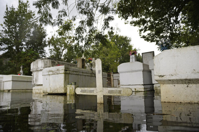 FILE - In this Aug. 26, 2020 file photo, a cemetery along Privateer Blvd. in Barataria, La. is inundated in water as water levels surge before Hurricane Laura hit the area, in Barataria, La. Louisiana officials say Hurricane Laura damaged nearly 1,900 graves, but they've received fewer than 25 requests for help with them. Louisiana Attorney General Jeff Landry says his office is taking the lead in finding and identifying displaced caskets, vaults, and remains, and returning them to their proper places. (Max Becherer/The Advocate via AP, File)