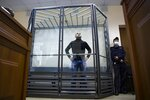"""FILE - In this June 2, 2021, file photo, Andrei Pivovarov, the leader of Open Russia group financed by Russian tycoon Mikhail Khodorkovsky, stands behind the glass during a court session in Krasnodar, Russia. Pivovarov, who had planned run for the Duma, was removed from a Warsaw-bound plane just before takeoff from St. Petersburg and taken to the southern city of Krasnodar. He was accused of supporting a local candidate last year on behalf of an """"undesirable"""" organization and jailed pending an investigation. (AP Photo/File)"""