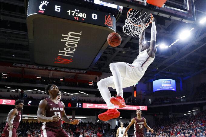 Cincinnati's Tre Scott dunks as Alabama A&M's Cameron Alford (13) watches during the first half of an NCAA college basketball game Thursday, Nov. 14, 2019, in Cincinnati. (AP Photo/John Minchillo)