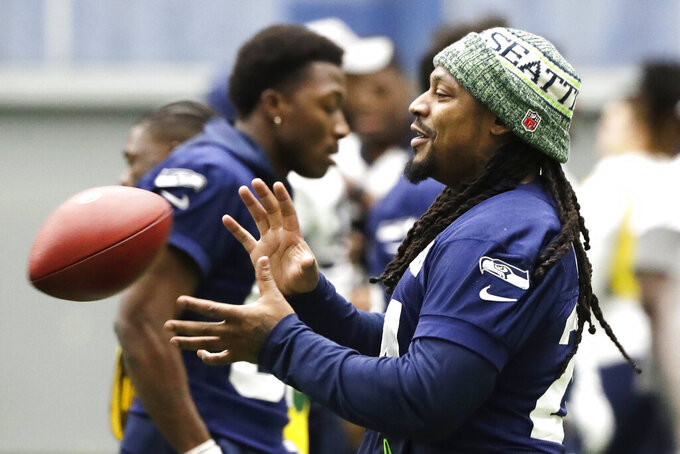 Seattle Seahawks running back Marshawn Lynch catches a football as he warms up for NFL football practice, Friday, Dec. 27, 2019, in Renton, Wash. The Seahawks will face the San Francisco 49ers Sunday, Dec. 29, 2019 in Seattle. (AP Photo/Ted S. Warren)
