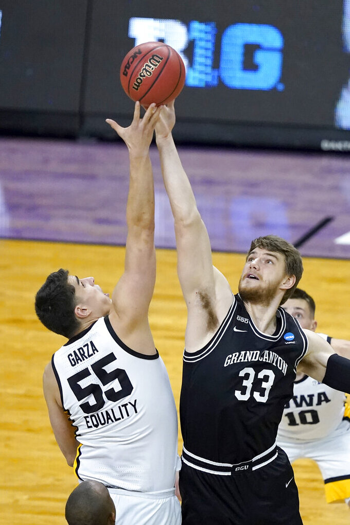 Iowa's Luka Garza (55) and Grand Canyon's Asbjorn Midtgaard battle for the opening tip during the first half of a first round NCAA college basketball tournament game Saturday, March 20, 2021, at the Indiana Farmers Coliseum in Indianapolis. (AP Photo/Charles Rex Arbogast)