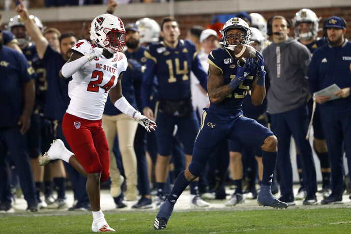 Georgia Tech wide receiver Malachi Carter (15) makes a catch for a long gain as North Carolina State cornerback Malik Dunlap (24) defends during the first half of an NCAA college football game Thursday, Nov. 21, 2019, in Atlanta. (AP Photo/John Bazemore)