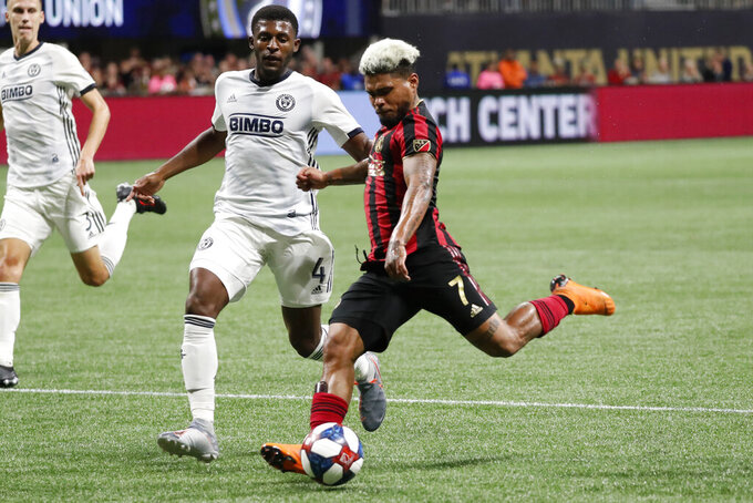FILE - In this Oct. 24, 2019, file photo, Atlanta United forward Josef Martinez (7) scores a goal as Philadelphia Union defender Mark McKenzie (4) defends during the second half of an MLS soccer Eastern Conference semifinal in Atlanta. One of the most dynamic strikers in Major League Soccer history, and the face of Atlanta United's stunning rise to the top of the league, Martinez missed nearly all of last season recovering from a serious knee injury. (AP Photo/John Bazemore, File)
