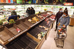 FILE - In this Jan. 25, 2020 photo, shoppers wearing face masks look for groceries near mostly empty produce shelves at a supermarket in Wuhan in central China's Hubei province, Saturday, Jan. 25, 2020. Complicated logistics are part of a daily flow of food and other goods authorities say is sustaining Wuhan and surrounding cities with a total of 50 million people. Most are blocked from leaving in the most sweeping disease-control measures ever imposed. (Chinatopix via AP, File)