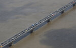 The Han River, swollen with floodwater, flows under a bridge in Seoul, South Korea, Thursday, Aug. 6, 2020. On Thursday, the state-run Han River Flood Control Office issued a flood alert near a key river bridge in Seoul, the first such advisory since 2011. (AP Photo/Lee Jin-man)