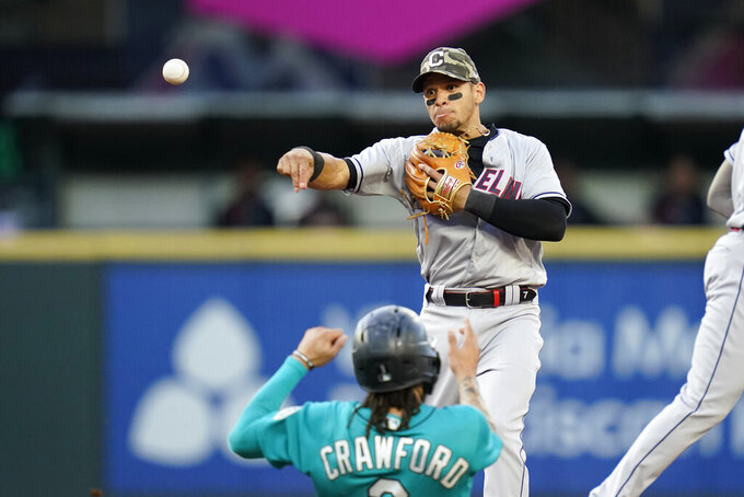 Cleveland Indians second baseman Cesar Hernandez throws to first base after forcing out Seattle Mariners' J.P. Crawford (3) at second base during the second inning of a baseball game Friday, May 14, 2021, in Seattle. Dylan Moore was out at first on the double play. (AP Photo/Elaine Thompson)