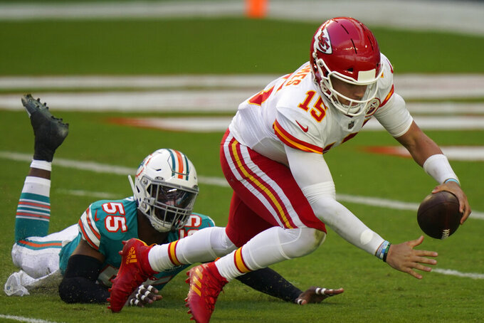 Kansas City Chiefs quarterback Patrick Mahomes (15) falls on the field after he was sacked by Miami Dolphins outside linebacker Jerome Baker (55), during the first half of an NFL football game, Sunday, Dec. 13, 2020, in Miami Gardens, Fla. (AP Photo/Lynne Sladky)