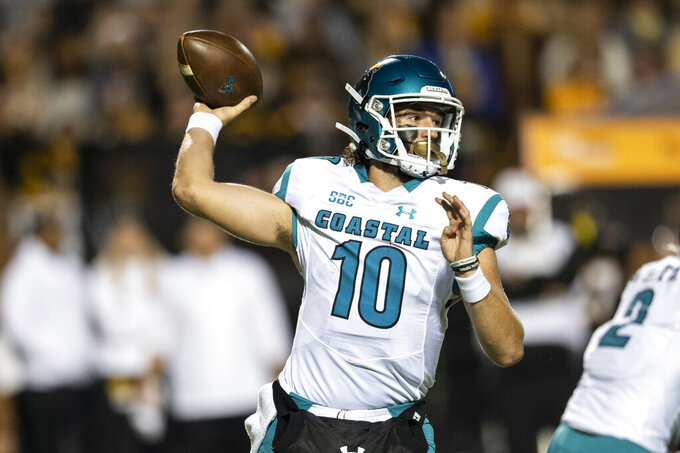 Coastal Carolina quarterback Grayson McCall (10) throws a pass during the first half of the team's NCAA college football game against Appalachian State on Wednesday, Oct. 20, 2021, in Boone, N.C. (AP Photo/Matt Kelley).