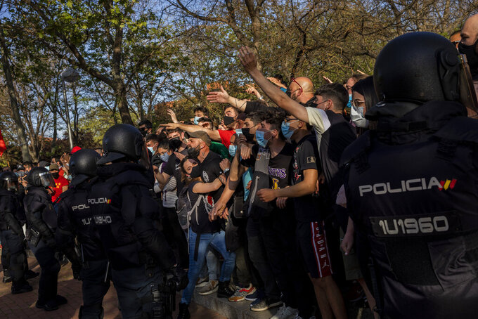 Left-wing protesters gather against a campaign event of the far-right Vox party in Madrid, Spain, Wednesday, April 7, 2021. Spanish police had to use batons on Wednesday to keep protesters away from supporters of the far-right Vox party at a campaign rally in Madrid. Scuffles started when the national leader of Vox, Santiago Abascal, approached a crowd which had gathered to protest the party rally in Madrid's working-class Vallecas neighborhood, a traditional left-wing bastion. Riot peace charged several hundred protesters to keep them away from Abascal and other members of his party campaigning for May 4 regional elections in the area including Spain's capital. (AP Photo/Bernat Armangue)