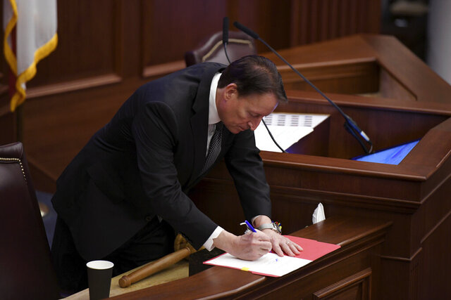 Senate president Bill Galvano, R-Bradenton, signs conference reports during session at the Capitol on Thursday, March 19, 2020 in Tallahassee, Fla. (AP Photo/Aileen Perilla)