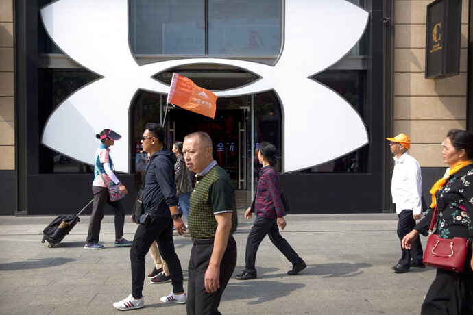 A Chinese tour guide leads a tour group past a store from American sportswear retailer Under Armour at an outdoor shopping area in Beijing, Tuesday, Sept. 25, 2018. A Chinese trade envoy said Tuesday that talks with Washington are impossible while the United States