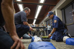 In this photo taken June 8, 2019, Luis Gonzalez, a Community Emergency Response Team instructor from the Los Angeles County Fire Department, showed trainees how to attach an automated external defibrillator during a CPR demonstration in Carson, California. As police and firefighter numbers dwindle, authorities urge personal responsibility. (Brigette Waltermire/News21 via AP)