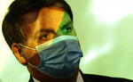 Brazil's President Jair Bolsonaro wears a mask amid the COVID-19 pandemic at the start of a ceremony where his nation's flag is projected over him in Brasilia, Brazil, Wednesday, Aug. 5, 2020. In May, facing urgent international demands for action after a string of massive wildfires in the Amazon, Brazilian President Jair Bolsonaro put the army in charge of protecting the rainforest. (AP Photo/Eraldo Peres)