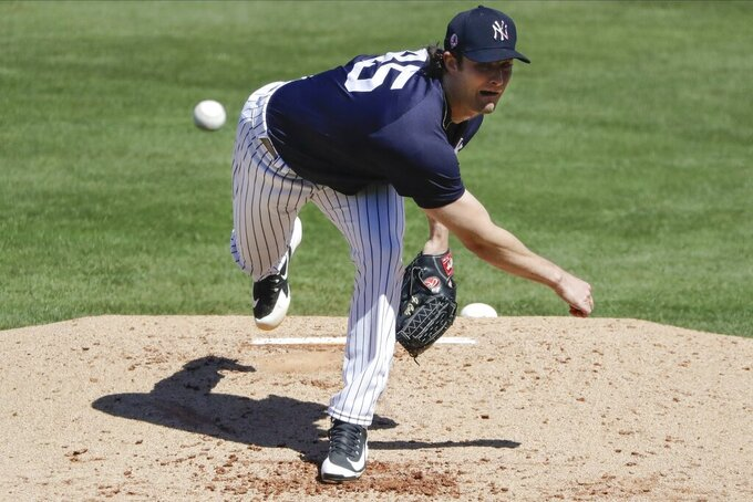 FILE - In this Feb. 29, 2020, file photo, New York Yankees' Gerrit Cole delivers a pitch during the third inning of the team's spring training baseball game against the Detroit Tigers in Tampa, Fla. Sixty-five players would earn at least $100,000 each time their team wins or loses if the pandemic-delayed major league season get under way, according to an analysis of their contracts by The Associated Press. Cole is scheduled to earn $222,222 for each game of a 162-game season. (AP Photo/Frank Franklin II, File)