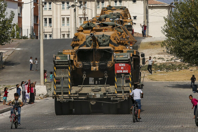 Local residents cheer, as Turkish army tanks are transported on trucks in the outskirts of the town of Akcakale, in Sanliurfa province, southeastern Turkey, at he border of Syria, Thursday, Oct. 17, 2019. U.S. Vice President Mike Pence, heading a delegation that includes Secretary of State Mike Pompeo and White House national security adviser Robert O'Brien, arrived in Turkey on Thursday, a day after Trump dismissed the very crisis he sent his aides on an emergency mission to douse.(AP Photo/Emrah Gurel)