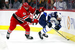 Carolina Hurricanes' Jordan Martinook (48) battles with Winnipeg Jets' Jansen Harkins (58) for the puck during the first period of an NHL hockey game in Raleigh, N.C., Tuesday, Jan. 21, 2020. (AP Photo/Karl B DeBlaker)