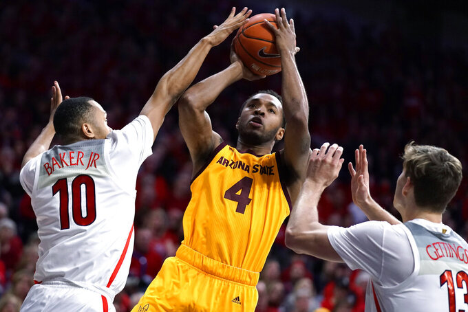 Arizona State forward Kimani Lawrence (4) shoots between Arizona guard Jemarl Baker Jr. (10) and Stone Gettings during the first half of an NCAA college basketball game Saturday, Jan. 4, 2020, in Tucson, Ariz. (AP Photo/Rick Scuteri)