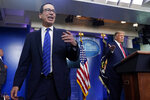 President Donald Trump listens as Treasury Secretary Steven Mnuchin speaks at a news conference in the James Brady Press Briefing Room at the White House, Monday, Aug. 10, 2020, in Washington. (AP Photo/Andrew Harnik)
