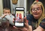 Darra Ann Morales shows a photo of her son Chaz Morales, with Chaz Jr., 10, at left, at the family home in Slidell, La., Wednesday, April 14, 2021. Darra Ann Morales is the mother and Chaz Jr. is the son of Chaz Morales, who is one of the crew members missing from the capsized vessel Seacor Power that departed from Port Fourchon when severe weather struck Tuesday. (Max Becherer/The Times-Picayune/The New Orleans Advocate via AP)
