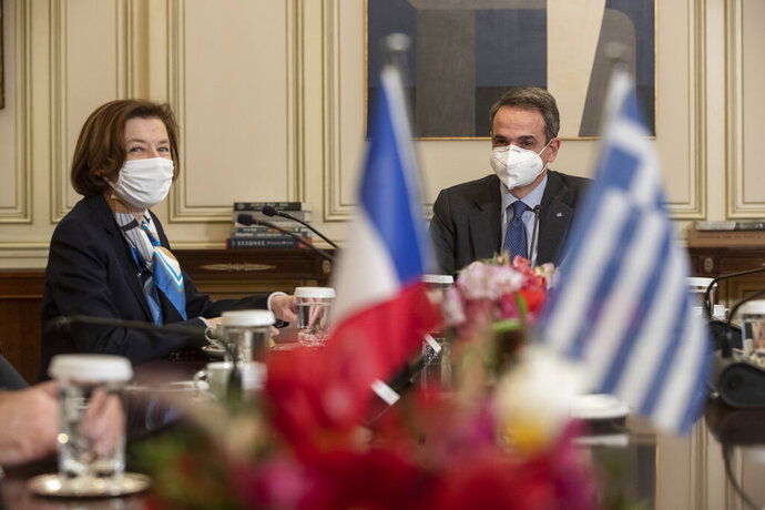 Greek Prime Minister Kyriakos Mitsotakis, right, speaks with French Defense Minister Florence Parly, during their meeting in Athens on Monday Jan. 25, 2021. Greece signed a 2.3 billion euro ($2.8 billion) deal with France Monday to purchase 18 Rafale fighter jets to address tension with neighbor Turkey. (AP Photo/Petros Giannakouris)