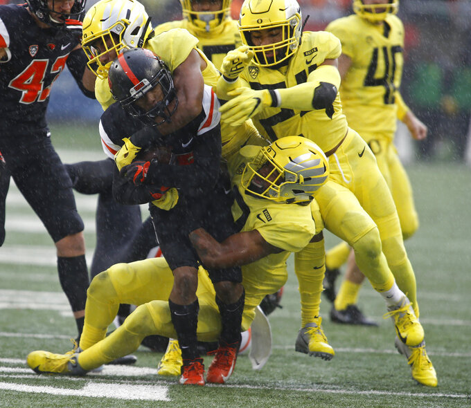 Oregon State kick returner Champ Flemings, center, get swarmed by Oregon defenders during the second half of an NCAA college football game in Corvallis, Ore., Friday, Nov. 23, 2018. Oregon won 55-15. (AP Photo/Timothy J. Gonzalez)