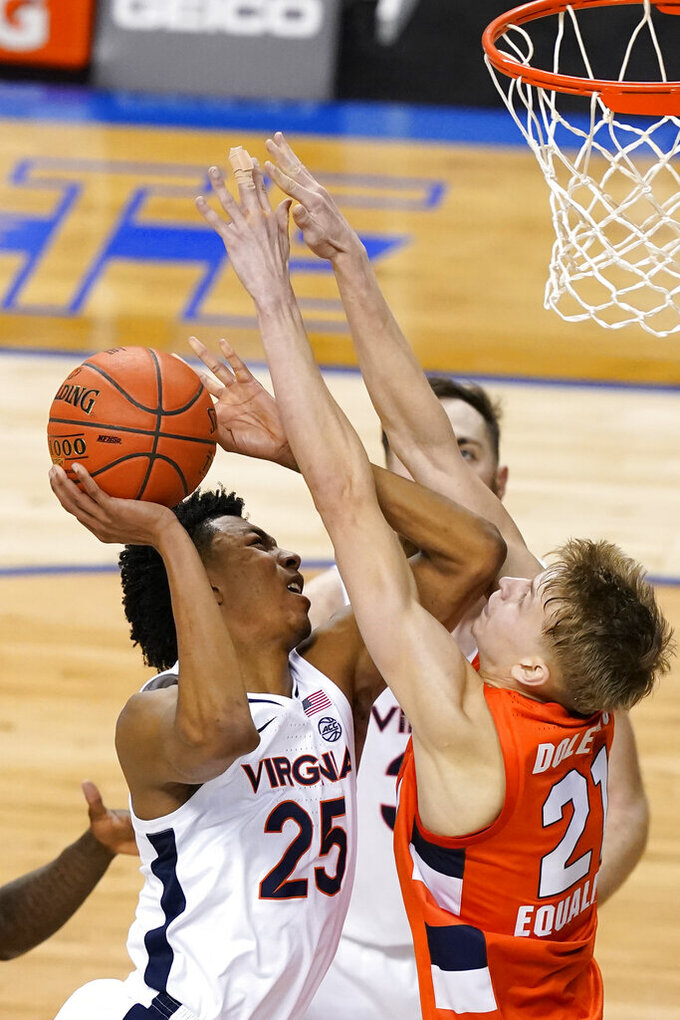Virginia guard Trey Murphy III (25) goes up for a shot as Syracuse forward Marek Dolezaj (21) defends during the second half of an NCAA college basketball game in the quarterfinal round of the Atlantic Coast Conference tournament in Greensboro, N.C., Thursday, March 11, 2021. (AP Photo/Gerry Broome)